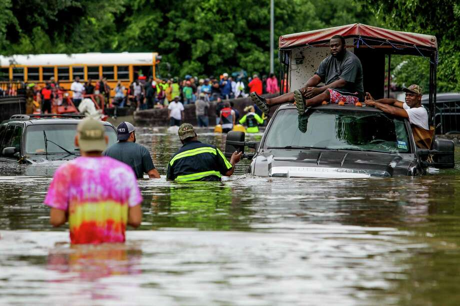 Good Samaritans who were trying to rescue others from the flooding in the Greenspoint area last week were forced to take shelter on top of their truck after it got stranded on Seminar Drive. Photo: Michael Ciaglo, Staff / © 2016 Houston Chronicle