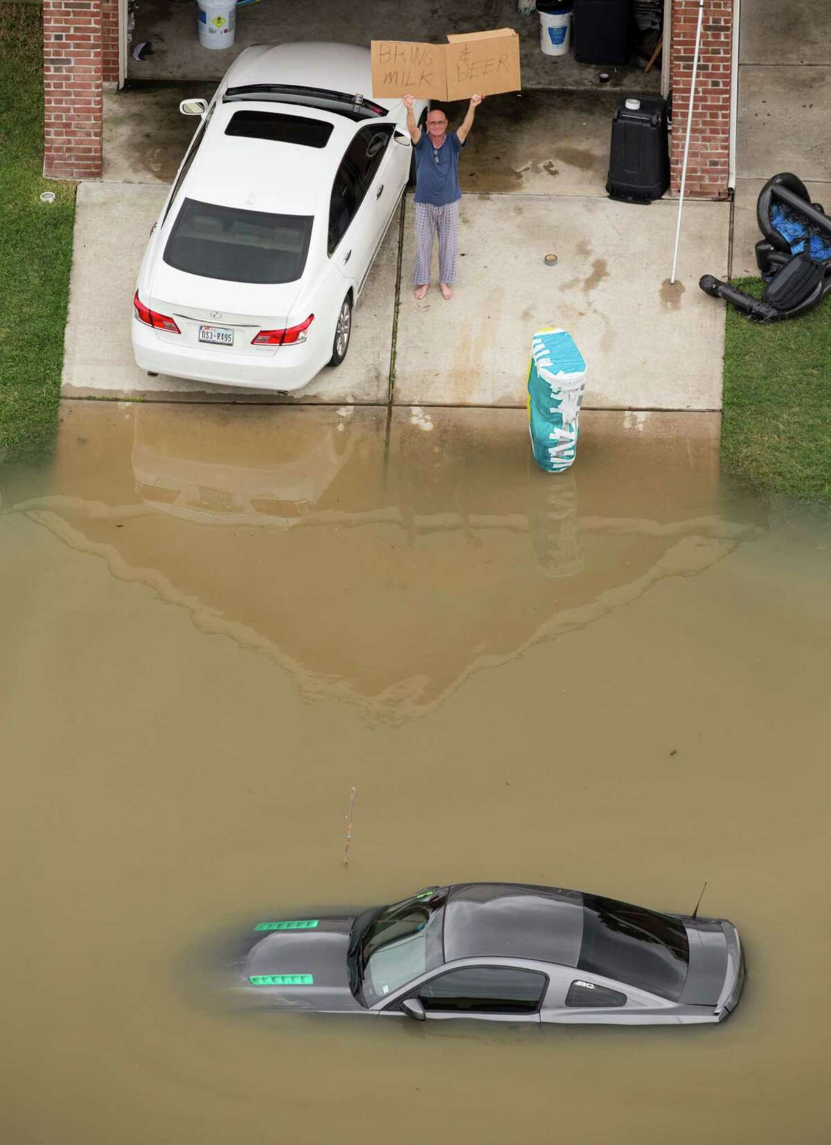 """A man holds up a sign saying, """"Bring Milk & Beer"""" as floodwaters creep close to a house last week in the Wimbledon Champions Park subdivision."""