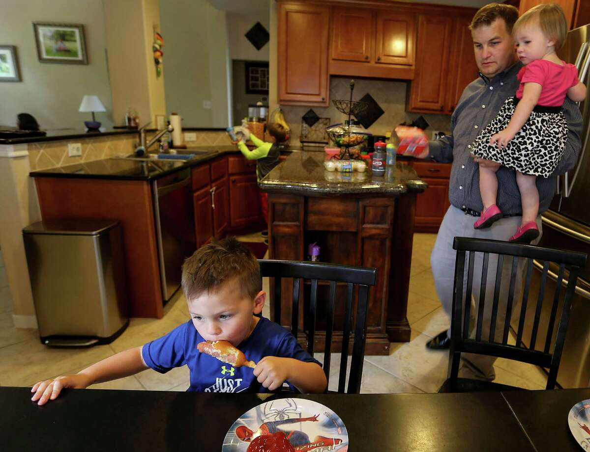 Shaun Conley in his Woodlands, Texas home with his children during lunch time. Conley, an engineer, was laid off and is currently trying to navigate the insurance system with his wife. (Elizabeth Conley / Houston Chronicle )