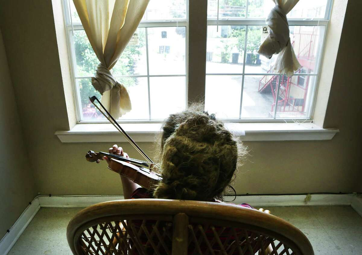 Xiao Xuan Zhu plays violin every day in her apartment at the boarding home on West Craig Place.
