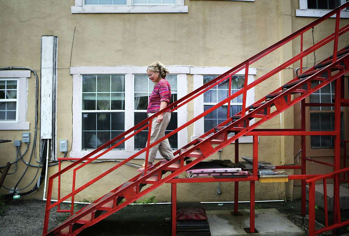 Xiao Xuan Zhu walks down the stairs from her apartment at the boarding home on West Craig Place on Thursday to get a snack in the kitchen.