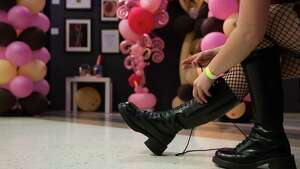 A woman ties on her boots during the Seattle Erotic Festival at the Seattle Center Exhibition Hall on Saturday, April 23, 2016.