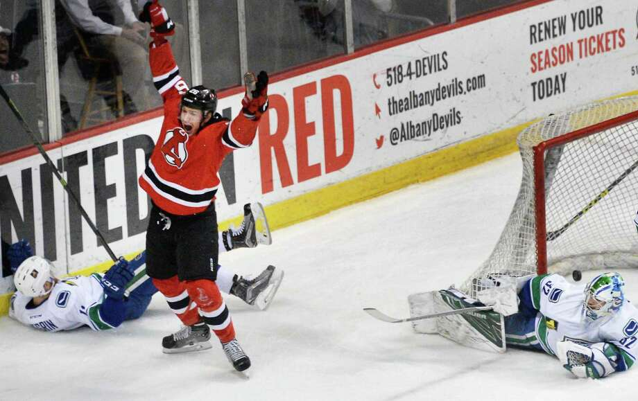 Albany Devils' #26 Ben Thomson celebrates his goal against  Utica Comets goalie Richard Bachman, right, during Game 2 of their playoff series sat the Times Union Center Saturday April 23, 2016 in Albany, NY.  (John Carl D'Annibale / Times Union) Photo: John Carl D'Annibale / 10036241A
