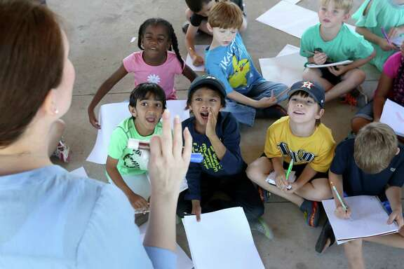 Students from Lisa Austin's first-grade class shout answers Friday during a math lesson in a park, where Pope Elementary teachers organized a special school day while their building was flooded.