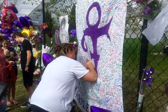 A woman writes on a memorial sheet adorned with the symbol Prince once used to identify himself on Saturday outside Paisley Park in Chanhassen, Minn. The music superstar was pronounced dead at his Paisley Park estate near Minneapolis on Thursday. He was 57.
