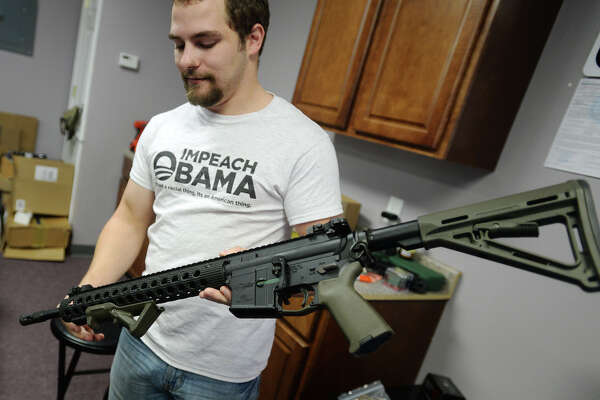 Derek Poe of Golden Triangle Tactical shows off an AR-15 from Troy Industries, which is the rifle that volunteers for Poe's border group will be carrying. Poe is organizing a group of volunteers to travel to the Texas-Mexico border. Poe says that not only will his store supply firearms and night vision equipment to volunteers, but the deployments will be a paying endeavor.  Photo taken Wednesday 8/27/14 Jake Daniels/@JakeD_in_SETX