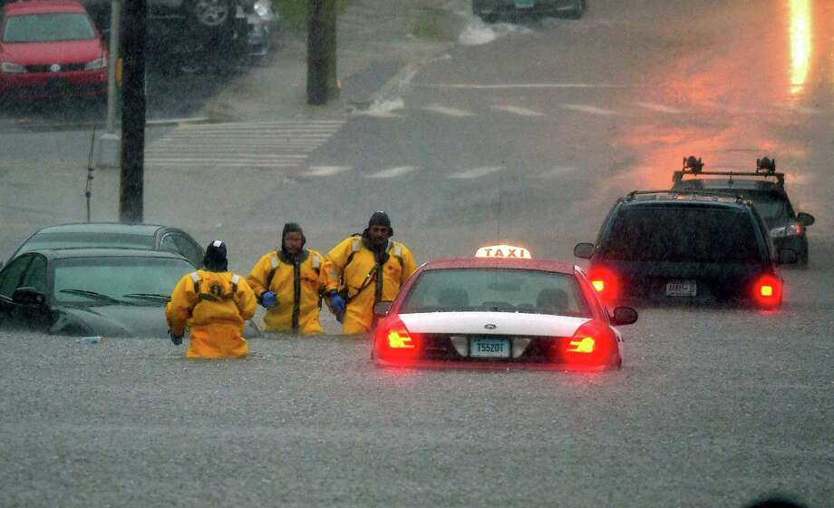Firefighters head for higher ground after checking flooded cars for occupants on Broad Street after a line of thunderstorms dumped torrential rain across the region flooding roads in New London, Conn., Thursday Sept. 10, 2015.  (Tim Cook/The Day via AP)  MANDATORY CREDIT Photo: Tim Cook / Associated Press / The Day