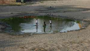 Indian men remove dead fish and try to rescue the surviving ones from the Vastrapur Lake that got dried up due to hot weather in Ahmadabad, India, Sunday, April 24, 2016. India is grappling with severe water shortages and drought affecting more than 300 million people, a quarter of the country's population. Thousands of distressed farmers have committed suicide, tens of thousands of farm animals have died, and crops have perished, with rivers, lakes and ponds drying up and groundwater tables sinking.