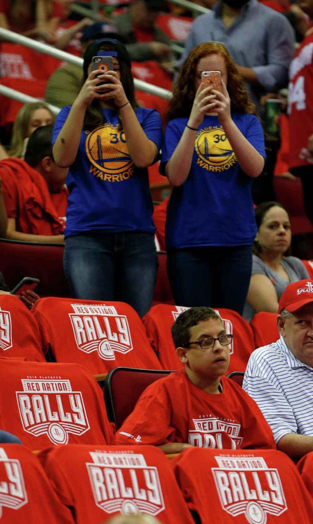 Golden State Warriors fans take photos before the start of game four of the first round of the NBA playoff series at Toyota Center, Sunday, April 24, 2016, in Houston.