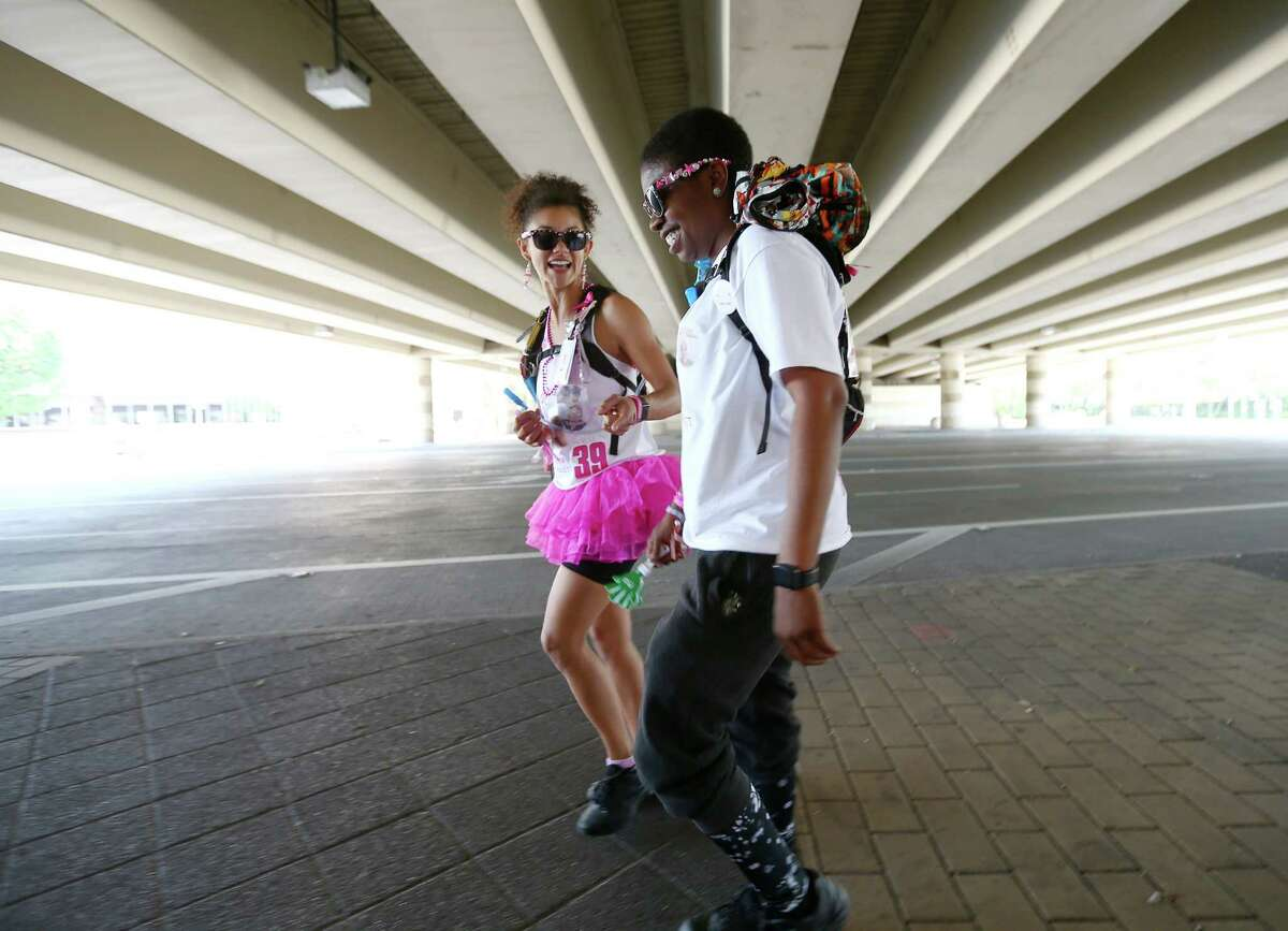 Nikki Tripplett, right, walks with her partner of seven years, Unique Roden, under IH-610 on Westheimer Road during the Avon 39 walk, Saturday April 23, 2016, in Houston. Tripplett was diagnosed with breast cancer last May, and wanted to complete the 39.3 mile walk before a right mastectomy and hysterectomy the following week.