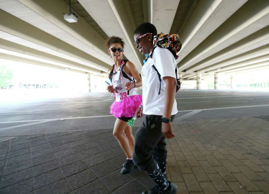 """Nikki Tripplett, right, walks with her partner of seven years, Unique Roden, under IH-610 on Westheimer Road during the Avon 39 walk, Saturday April 23, 2016, in Houston. Tripplett was diagnosed with breast cancer last May, and wanted to complete the 39.3 mile walk before a right mastectomy and hysterectomy the following week. """"For the first two months, I could keep walking. And then, thatÕs when chemo was starting, and as much as I wanted to walk, I just couldnÕt. What normally would be a 10 minute walk for us would be 30-45 minutes to the same stop sign, and when I would get back, I was done,"""" Tripplett said. Photo: Jon Shapley, Houston Chronicle / © 2015  Houston Chronicle"""