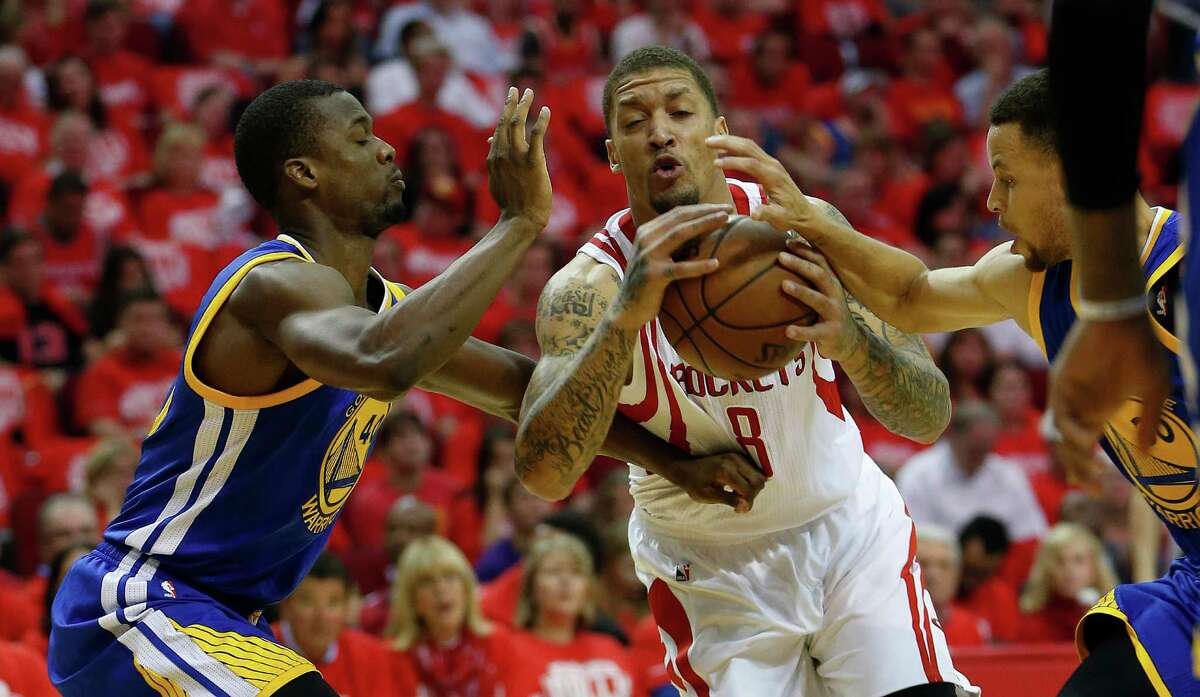Houston Rockets forward Michael Beasley (8) tries to make it to the basket against Golden State Warriors forward Harrison Barnes (40) and guard Stephen Curry (30) during the first half of game four of the first round of the NBA playoff series at Toyota Center, Sunday, April 24, 2016, in Houston.