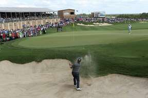 Charley Hoffman, of Las Vegas, Nevada, blasts out of an bunker on the 18th green during the final day of the Valero Texas Open at TPC San Antonio, April 24, 2016. The Valero Texas Open 19th Hole Fiesta celebration unfolds after the last putt of the golf tournament's third round.