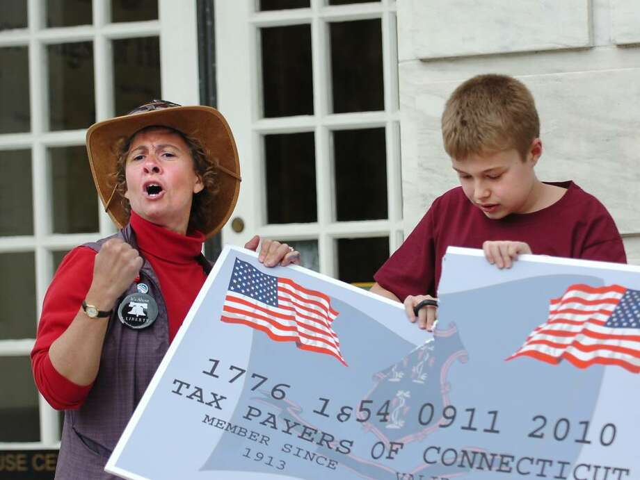 Local Tea Party organizer, Monique Thomas of Greenwich, left, shouts as Mitchell Slauson, 12, of Naugatuck, Conn., right, cuts up a representation of government credit card, during a Tea Party rally protesting government spending on tax filing deadline day, Thursday evening, April 15, 2010, in front of Greenwich Town Hall. Photo: Bob Luckey / Greenwich Time