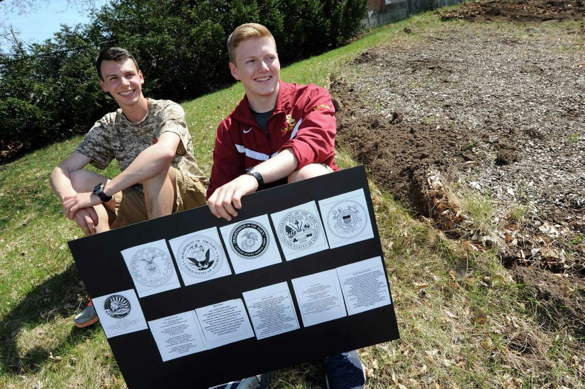Project manager John Lawlor, 18, right, joins John Cogan, 17, president of Colonie High's iCARE program, on the future Hill of Heroes on Thursday, April 21, 2016, at Colonie High in Colonie, N.Y. Lawlor, a member of the Air National Guard, holds a layout of the military emblems and creeds that will be placed in the Hill of Heroes. (Cindy Schultz / Times Union)