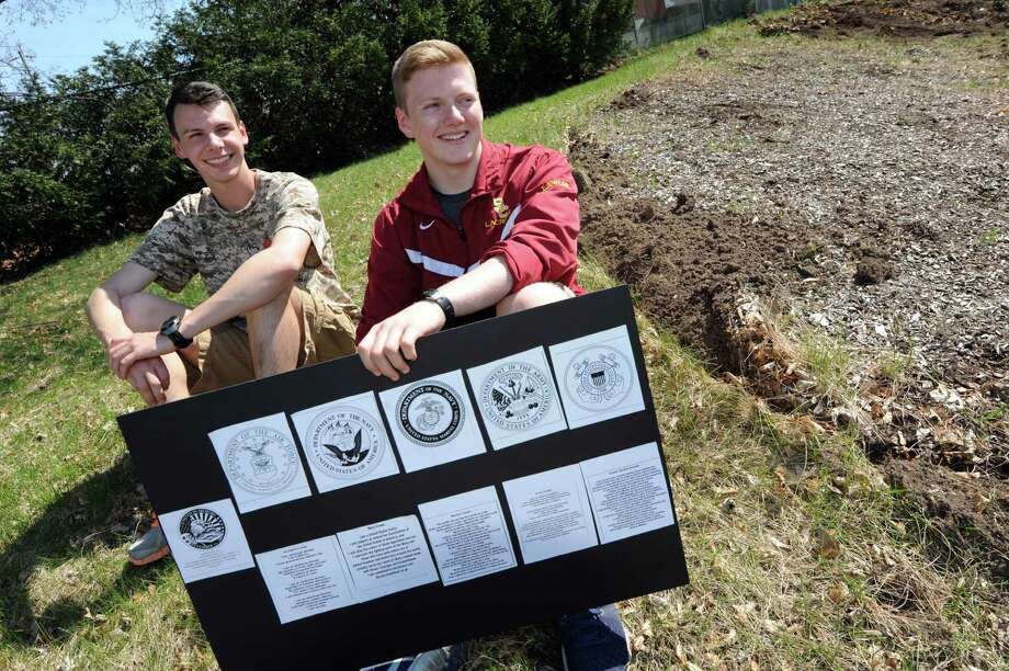 Project manager John Lawlor, 18, right, joins John Cogan, 17, president of Colonie High's iCARE program, on the future Hill of Heroes on Thursday, April 21, 2016, at Colonie High in Colonie, N.Y. Lawlor, a member of the Air National Guard, holds a layout of the military emblems and creeds that will be placed in the Hill of Heroes. (Cindy Schultz / Times Union) Photo: Cindy Schultz / Albany Times Union
