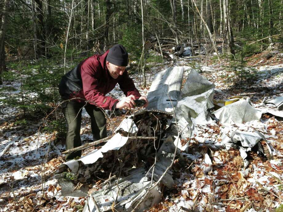 """In this April 3, 2016 photo, Scott Van Laer photographs pieces of a Cessna 207 that crashed into an Adirondack mountainside in 1970 in New York. The New York forest ranger is documenting dozens of plane crash sites in the Adirondack Mountains with plans for a book for fellow """"wreck chasers"""" and hikers. (AP Photo/Mary Esch) ORG XMIT: RPME101 Photo: Mary Esch / ap"""