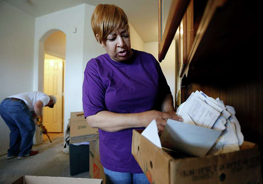 Shirley Sawyer looks through a box of personal items that were damaged in this week's floods as Foundry United Methodist Church members help her to remove flood-damaged items and sheetrock on Sunday. Photo: James Nielsen, Staff / © 2016  Houston Chronicle