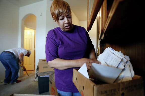 Shirley Sawyer looks through a box of personal items that were damaged in this week's floods as Foundry United Methodist Church members help her to remove flood-damaged items and sheetrock on Sunday.