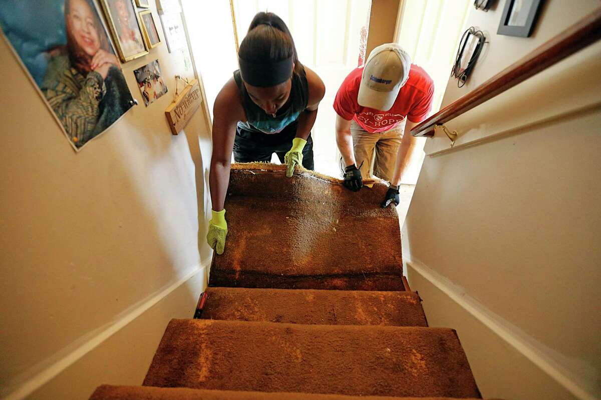 Shira Patton, left, removes flooded carpets from her grand-mother's home Sunday with help from Foundry United Methodist Church member Rob Calbat.