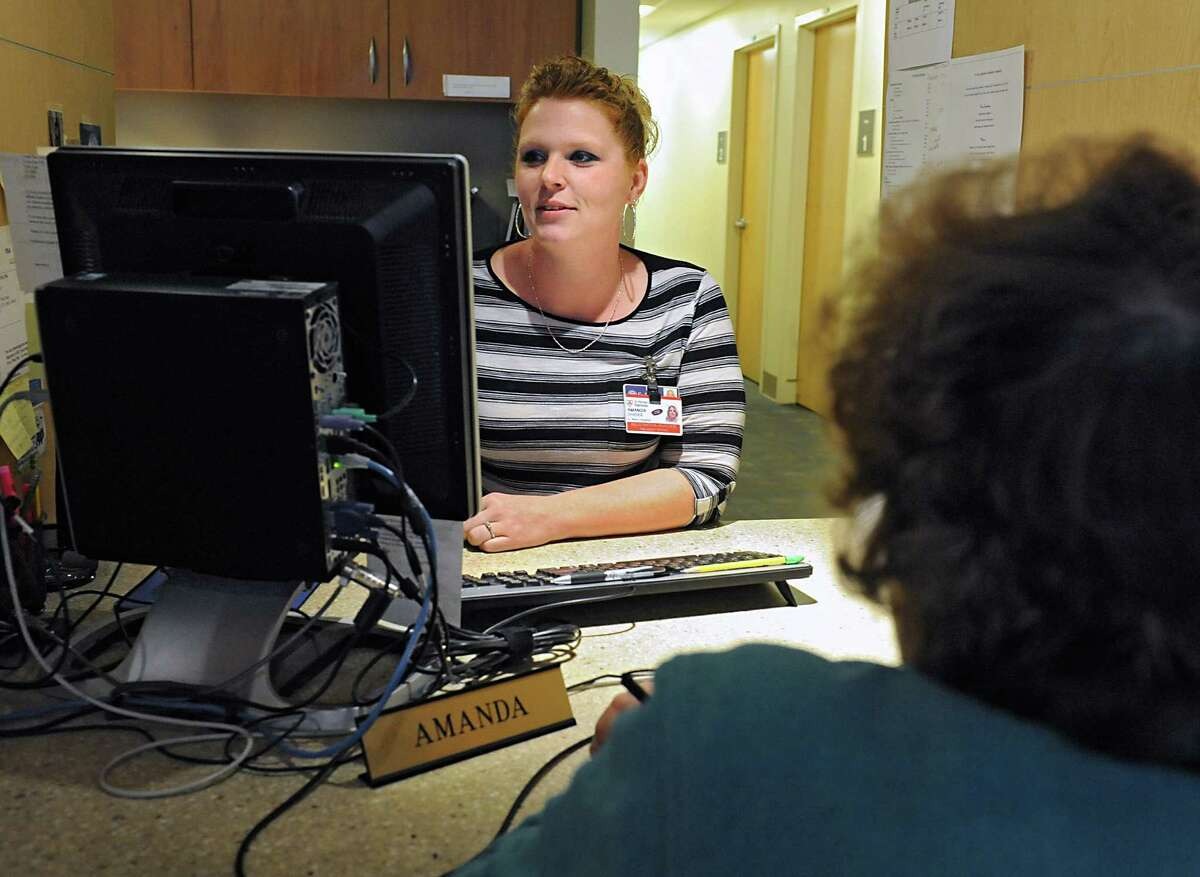 Registration associate Amanda Shader helps a patient at the admissions desk at St. Peter's Hospital on Friday, April 22, 2016 in Albany, N.Y. (Lori Van Buren / Times Union)