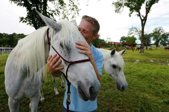 Justin Nelzen, 39, a veteran who served in Afghanistan, reconnects with Montego, a horse he helped save during last Monday's flood. Nelzen, below in red vest, rescued 11 horses from Cypress Creek with the help of other volunteers along with the 10 to 15 animals he saved on his own.