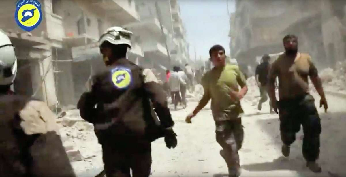In this image made from video posted online by the Syrian Civil Defense White Helmets, Civil Defense workers run after airstrikes and shelling hit Aleppo, Syria, Sunday, April 24, 2016. Air strikes and shelling pounded Aleppo for a third straight day Sunday, killing two young siblings and more than a dozen others in Syria's largest city and former commercial capital.