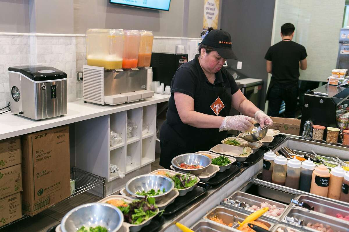Yamileth Cruz Sanchez scoops toppings on a poke bowl at Pokeatery in San Mateo.