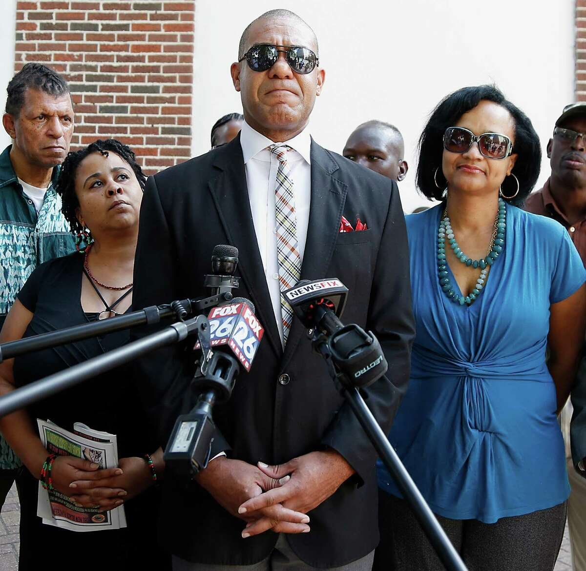Former Houston City Councilman Jarvis Johnson center, speaks during a press conference as Johnson wife Charlene Johnson right, and Krystal Muhammad left, look on, Johnson was pulled over on September the 13th Johnson by a Precinct 1 Deputy Constable for a traffic violation Thursday, Oct. 9, 2014, in Houston. Johnson says he was held a gunpoint, slapped and robbed of $2,500 cash a Precinct 1 Deputy Constable pulled who Johnson over for allegedly speeding. ( James Nielsen / Houston Chronicle )