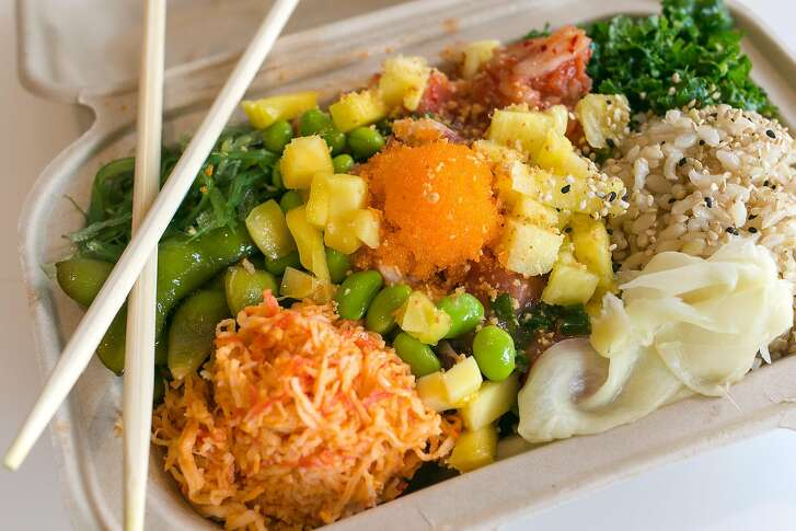 A custom poke bowl with toppings including spicy crab salad, seaweed salad, pickled ginger, kimchi.