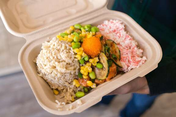 A customer holds his bowl of brown rice, edamame, corn, tuna, and crab salad.