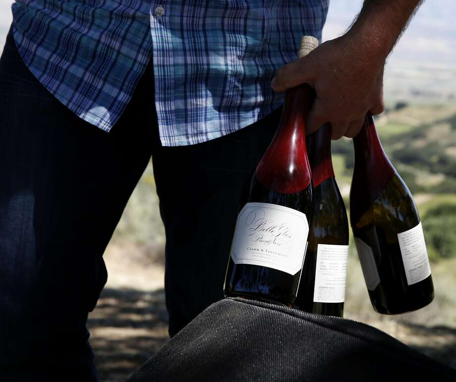 Joe Wagner carries three mostly empty bottles of Belle Glos wine after a tasting in the Las Alturas vineyard at the Santa Lucia Highlands in Monterey County. Photo: Connor Radnovich, The Chronicle