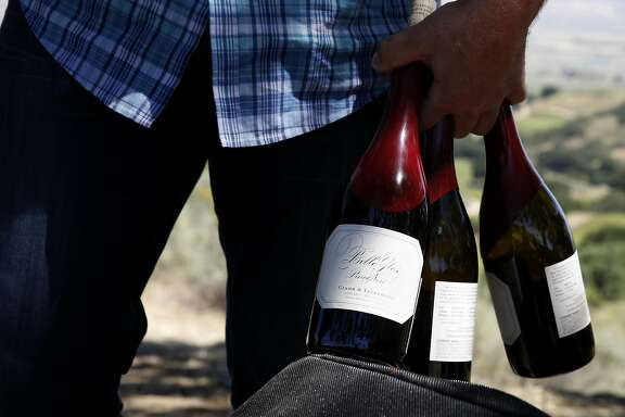 Joe Wagner carries three mostly empty bottles of Belle Glos wine after a tasting at a picnic table in the Las Alturas vineyard at the Santa Lucia Highlands in Monterey County, California, on Monday, April 18, 2016.