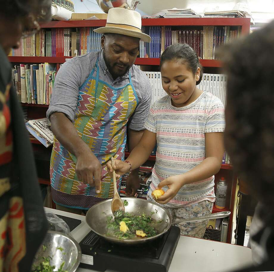 Chef Bryant Terry teaches Kanesha Harris, 11, how to cook vegetables at Meadows Livingstone elementary school in S.F. Photo: Liz Hafalia, The Chronicle