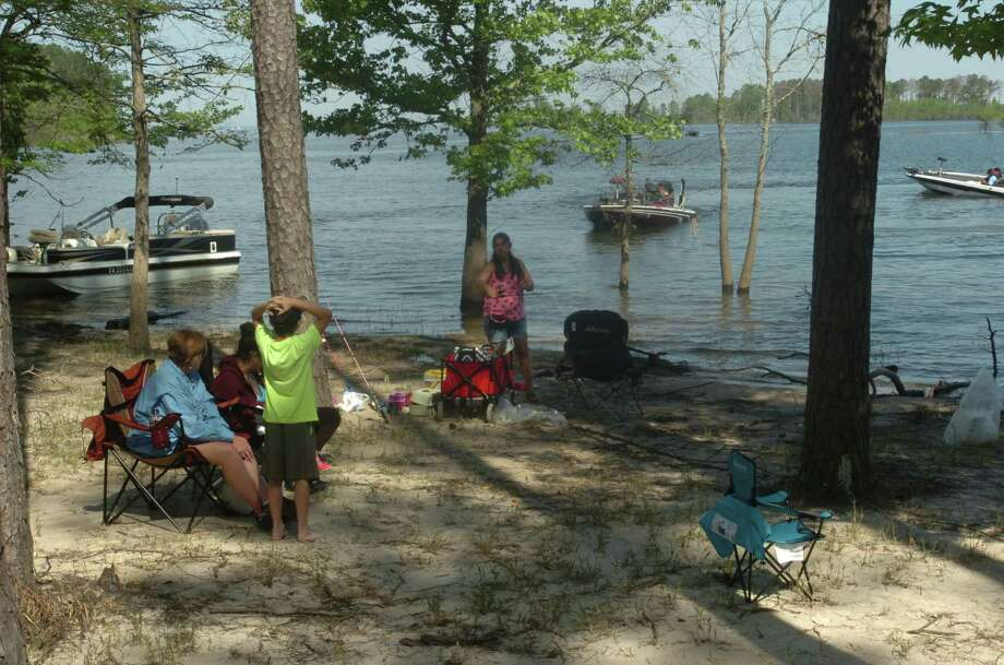 Amber Orchoski sits with her family on the Sam Rayburn beach as the anglers arrive. Photo: Brooks Kubena