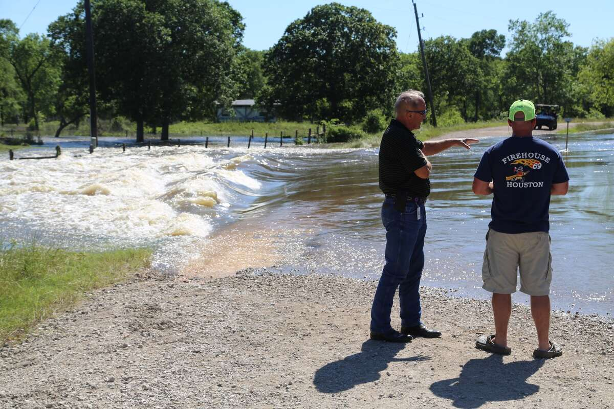 James R. Wenzel, a Fort Bend County official, talks to a resident of the Tierra Grande subdivision as water rushes across a low-water crossing in the Tierra Grande subdivision last Friday. (Mike Snyder/Houston Chronicle)