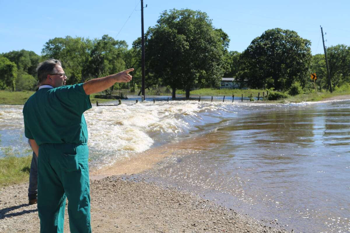 Greg Watson points to water from the swollen San Bernard River, which flooded the only road leading to his home. Watson was separated from his wife and children for several days. (Mike Snyder/Houston Chronicle)