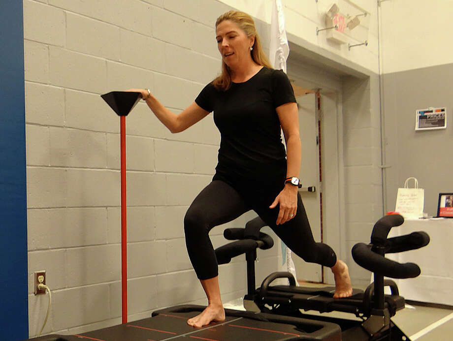 Debbie Wilhelmy of CoreMotion demonstrates an exercise machine at the Health and Wellness Expo sposnored Sunday by the Fairfield YMCA and Fairfield Chamber of Commerce. Photo: Fairfield Citizen / Mike Lauterborn / Fairfield Citizen