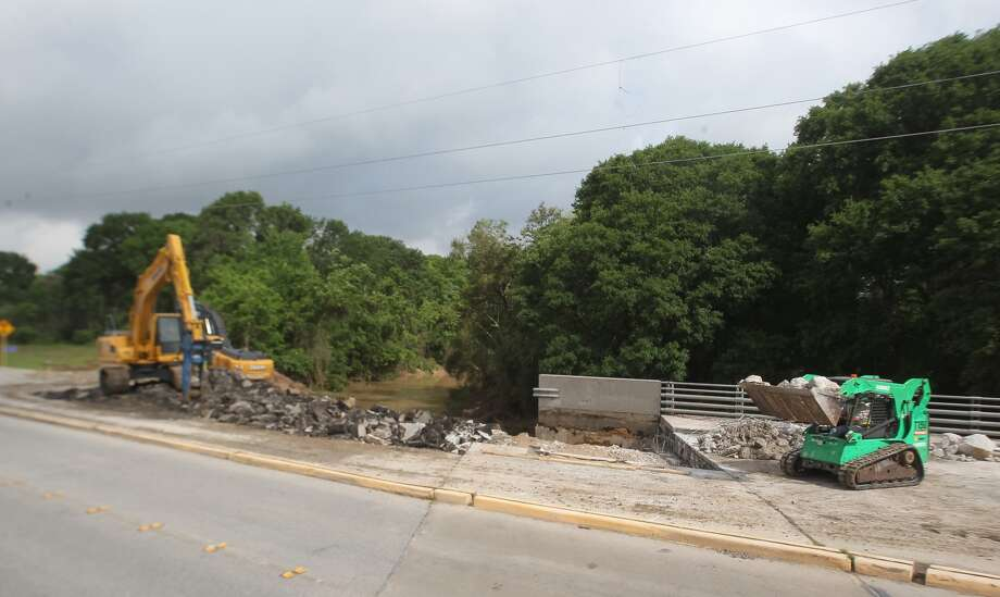 Work crews were busy Monday morning repairing damage to Clay Road near South Mayde Creek after heavy rain pounded northwest County during historic rainfall and massive flooding last week. (Steven Gonzales/HC)