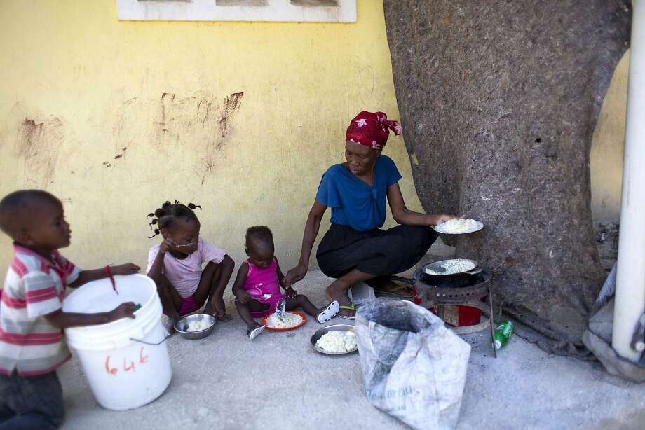 Three children of Jesula Gelin, a deaf woman who was killed, eat rice in the village of Leveque, Haiti. Photo: Dieu Nalio Chery, Associated Press