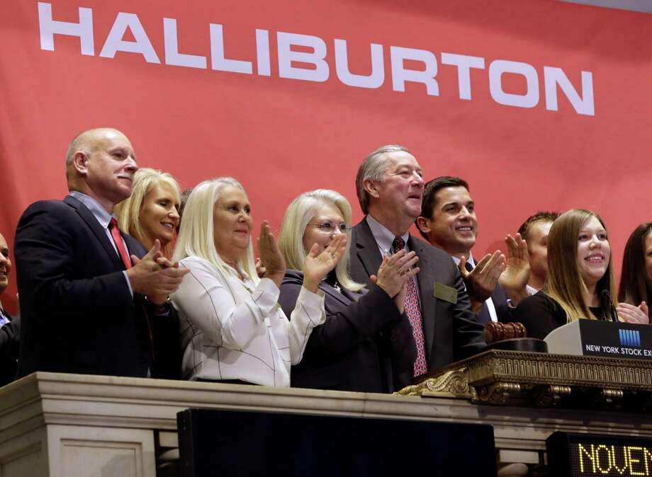 Halliburton Chairman, President and CEO David Lesar, third from right, rings the New York Stock Exchange opening bell in November 2014. Halliburton Co.'s has delayed releasing its first-quarter earnings, raising doubts over the prospects for a takeover of rival Baker Hughes Inc. Photo: Richard Drew /AP / AP