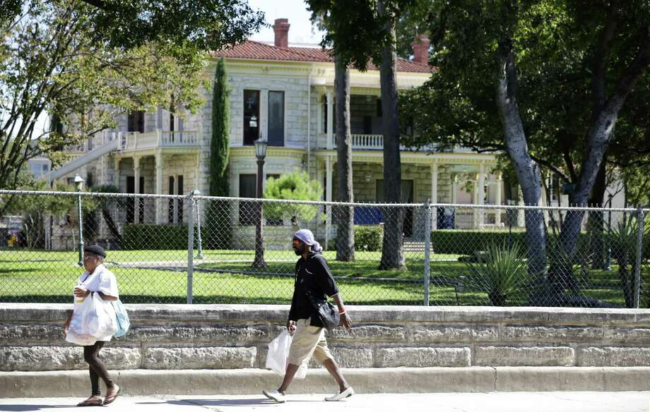 Pedestrians walk along the historic wall on Flores Street in front of the Commander's House on H-E-B's headquarter property between Cesar Chavez and Arsenal in 2013. Photo: Bob Owen /San Antonio Express-News / ©2013 San Antonio Express-News