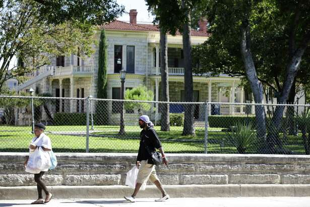 Pedestrians walk along the historic wall on Flores Street in front of the Commander's House on H-E-B's corporate campus.
