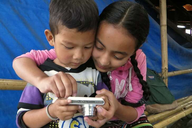 Children living in Camp Hope in Kathmandu experiment with digital cameras that were donated as part of an art project.