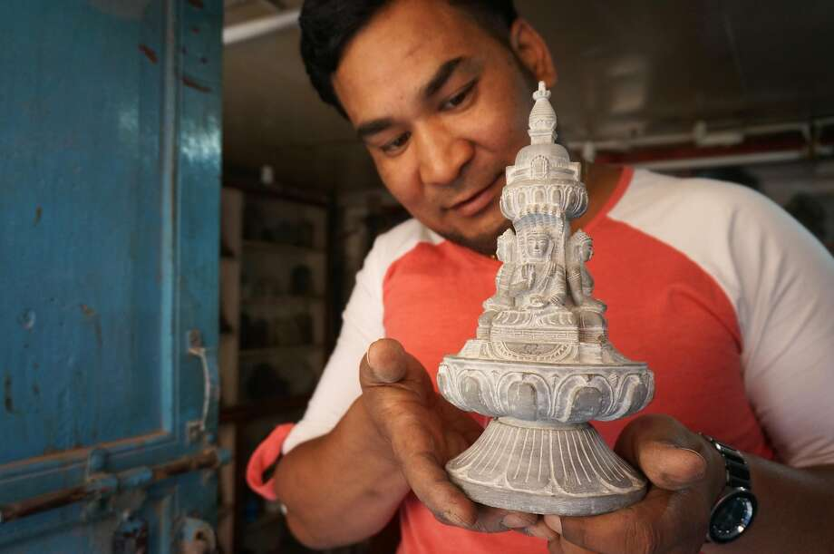 Sanu Vajracharya, whose family has been sculpting for several generations, shows off a work in Patan. Photo: Jeff Greenwald, Special To The Chronicle