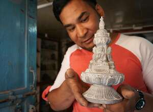 Sanu Vajracharya, whose family has been sculpting for several generations, shows off a work in Patan.