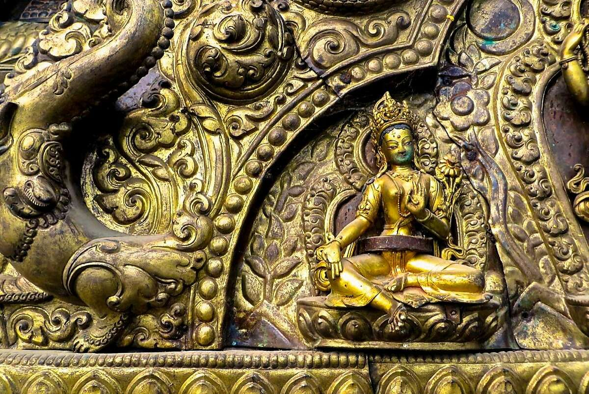 Protected from art thieves by a metal belt, a lost-wax statue of Tara bestows blessings from a repouss� panel in the Kathmandu Valley.