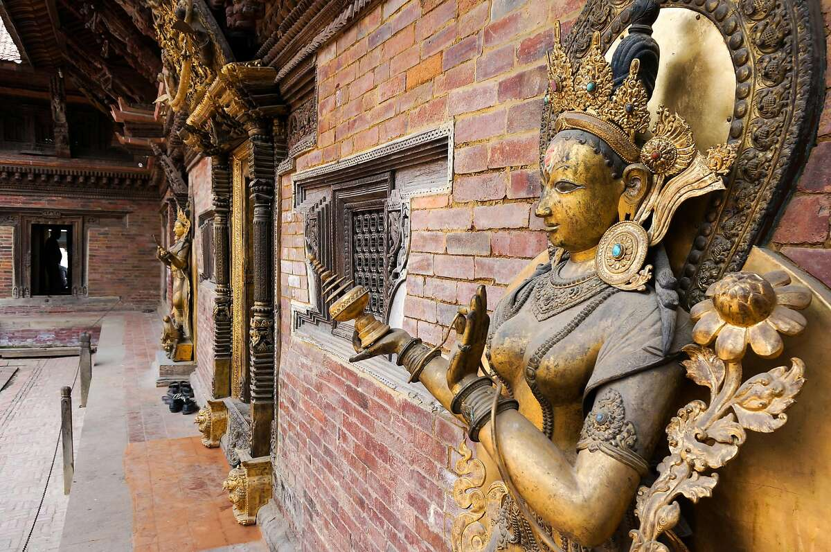 Ancient gilded statues of the goddess Tara, in the restored brick courtyard of Patan's ancient palace.