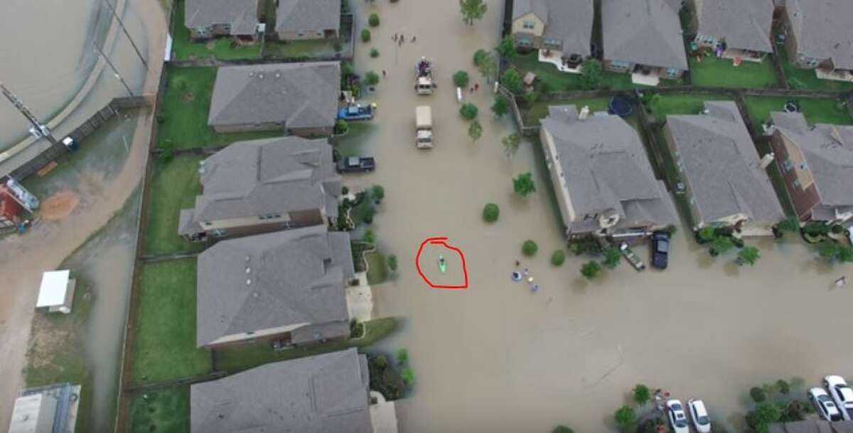 A boater paddles (red circle) through floodwaters in a Brookshire neighborhood.