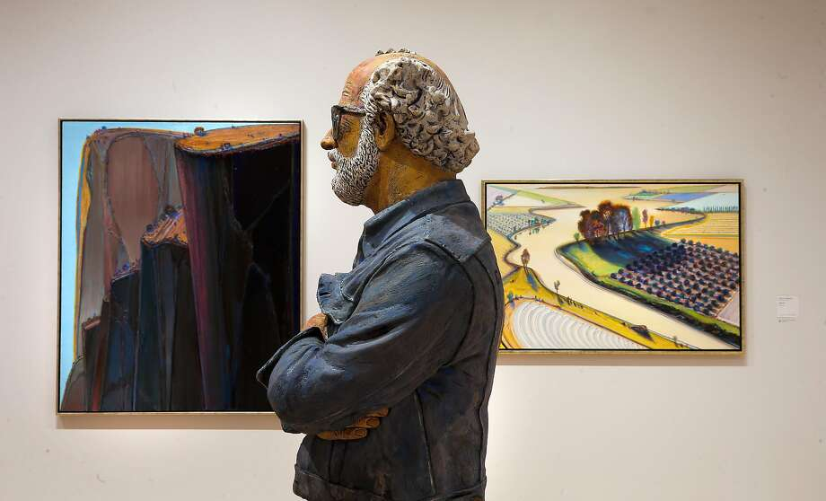 "Wayne Thiebaud artwork ""Canyon Mountains, (left) and ""Flatland River"" frame a self portrait sculpture by Robert Arneson, at the newly completed San Francisco Museum of Modern Art addition in San Francisco, California as seen on Fri. April 22, 2016. Photo: Michael Macor, The Chronicle"